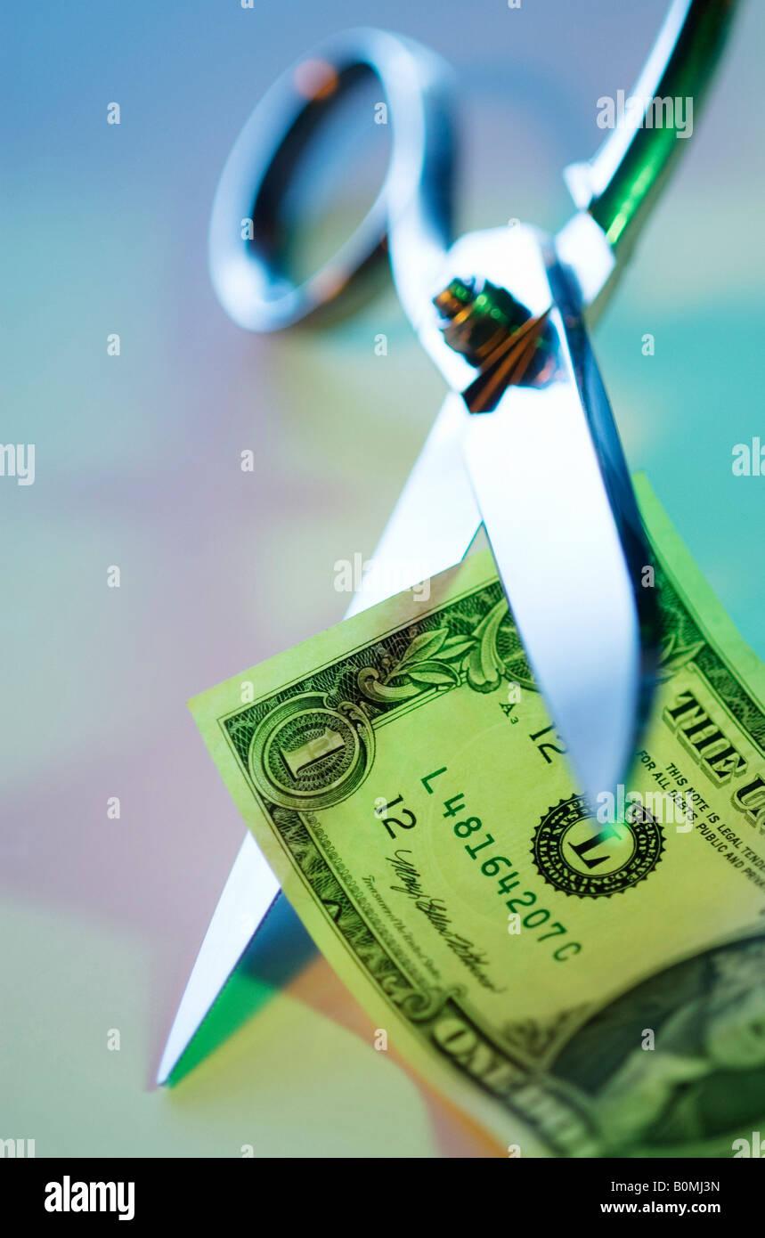 CRASH ECONOMY DEVALUATION CONCEPT. SCISSORS CUTTING US DOLLAR BANKNOTE BILL Stock Photo