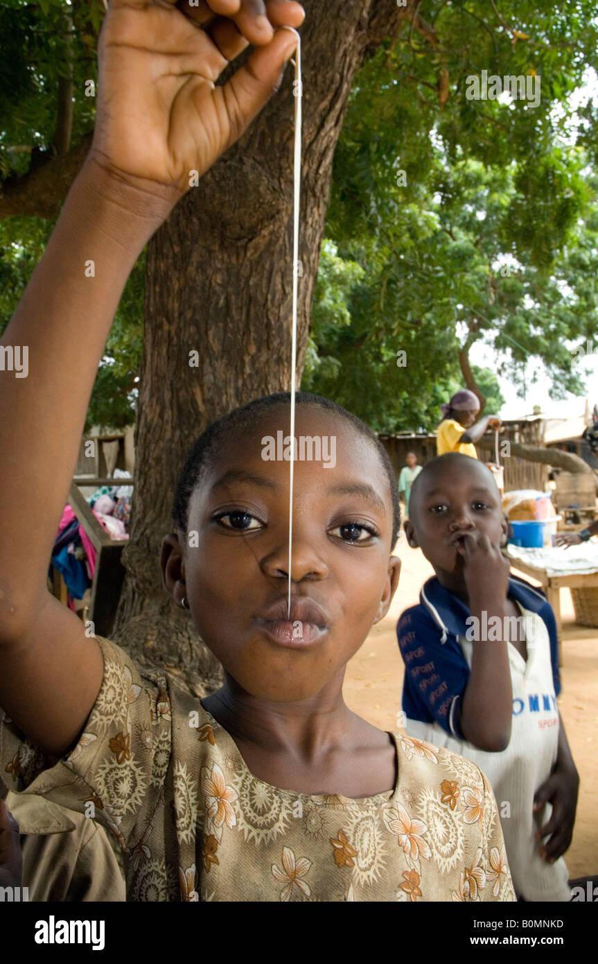 Girl pulling chewing gum, Kuluedor, Ghana - Stock Image