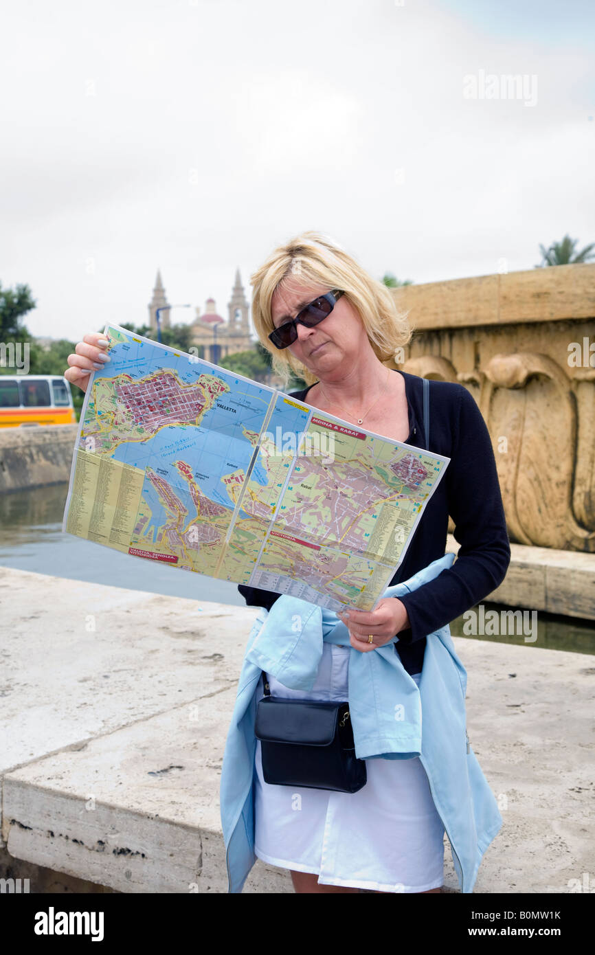 Female tourist reading and checking city map in Valetta Malta - Stock Image