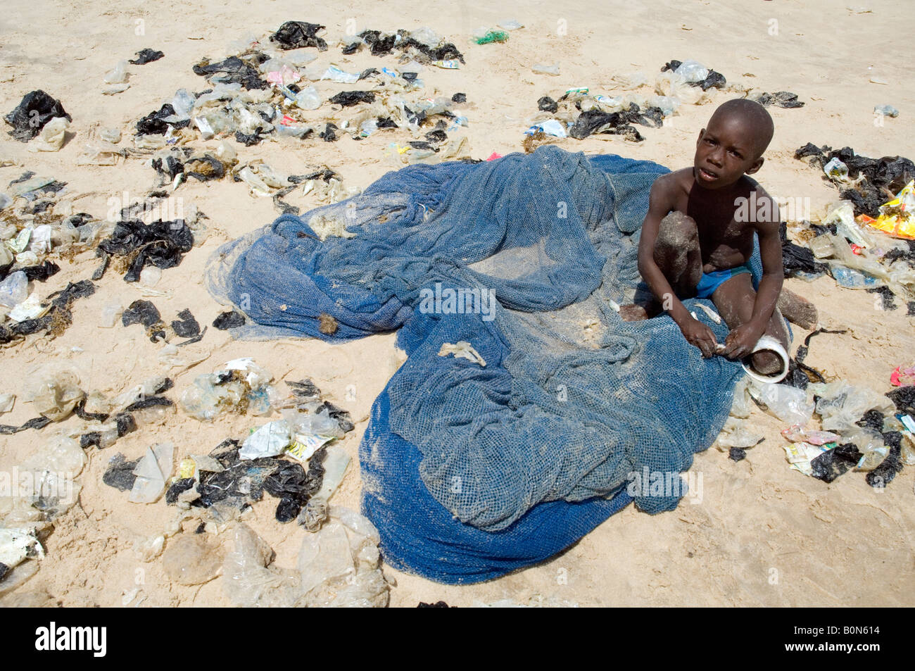 Boy removes plastic waste caught in a fishing net, east of Accra, Ghana - Stock Image