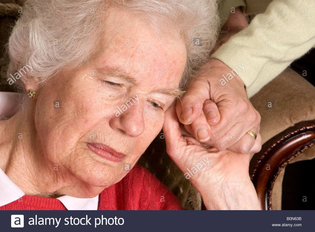Old woman being comforted. - Stock Image