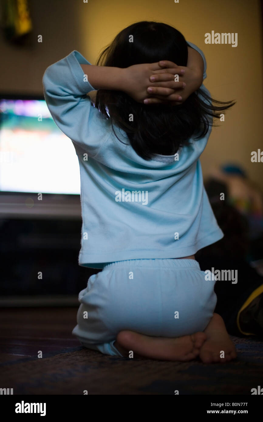 Girl age four watches sunday morning chlidren's television - Stock Image