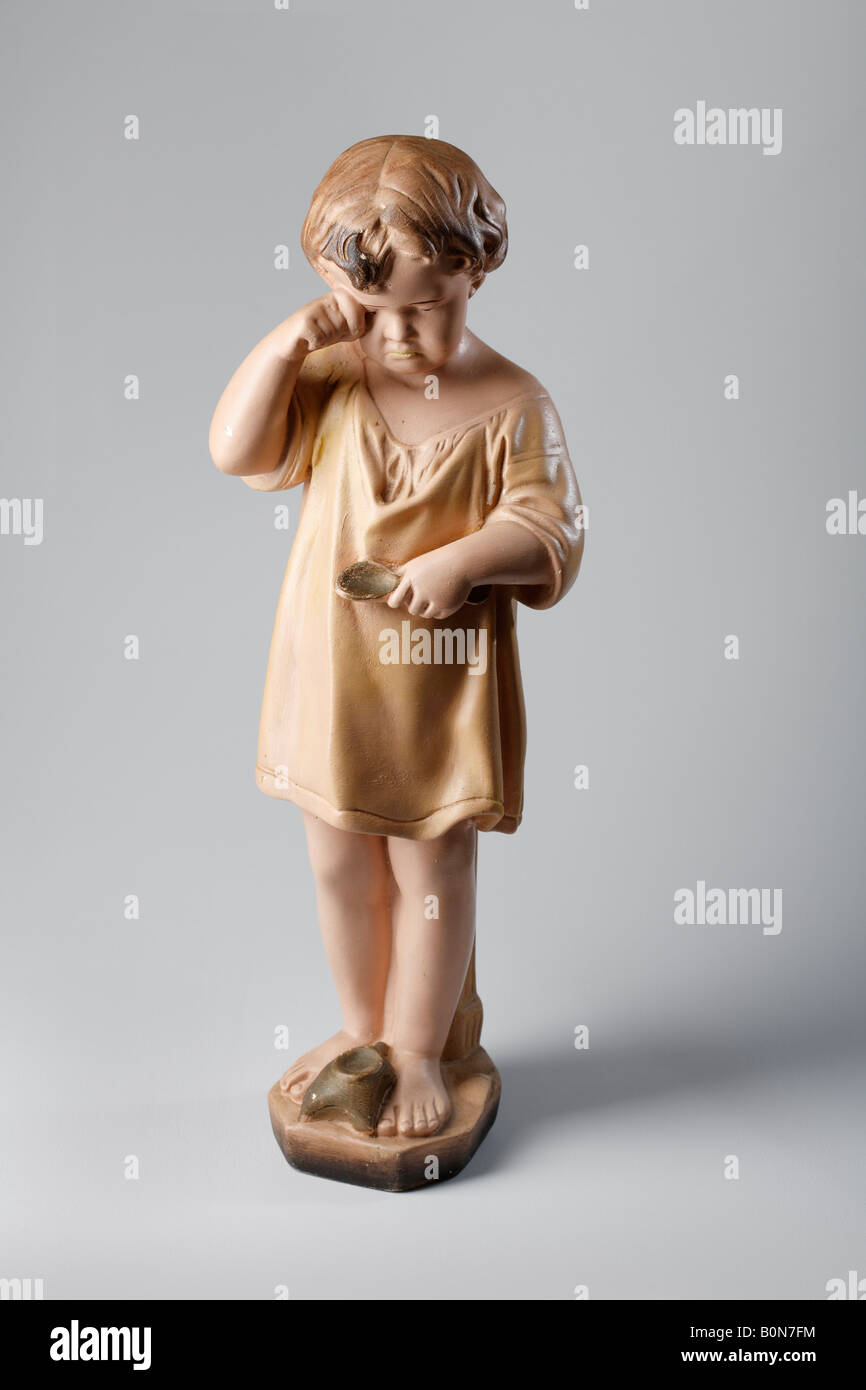 Kitschy small statue of a crying child - Stock Image