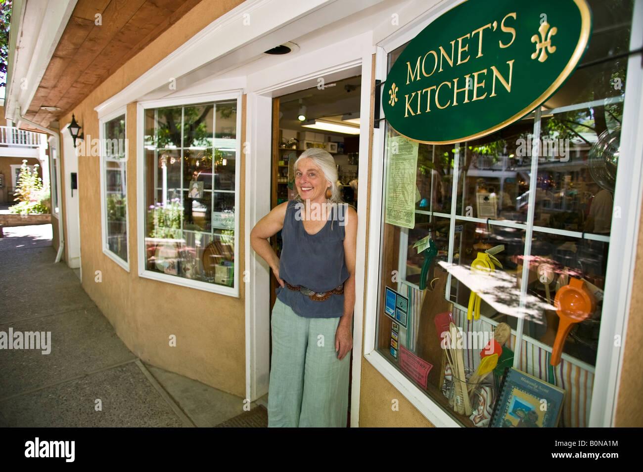 Portrait of female sales person in kitchen accessory store. - Stock Image