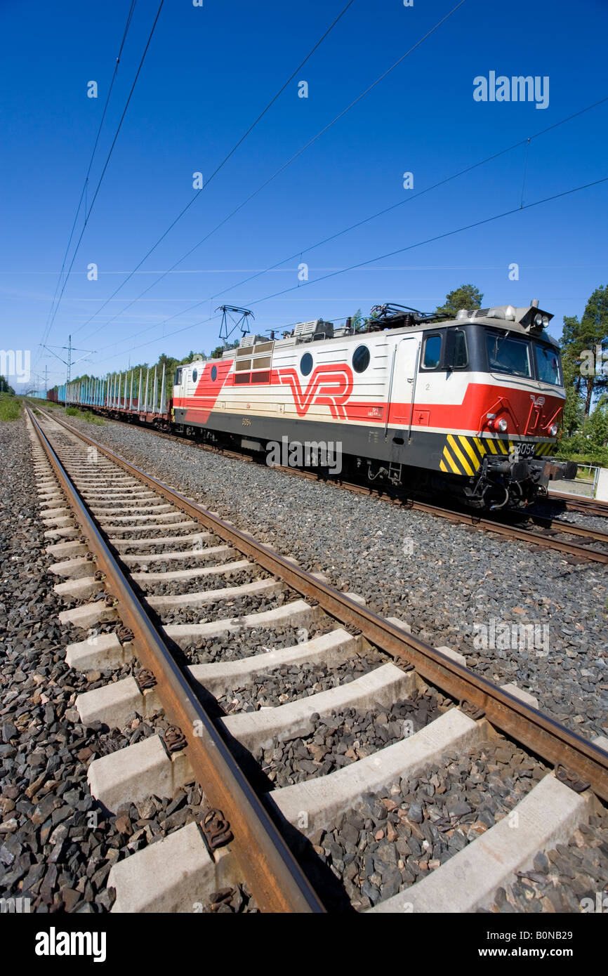 Long cargo train with electric locomotive and flatcars for log transport . Modern concrete sleepers ( ties ) on - Stock Image