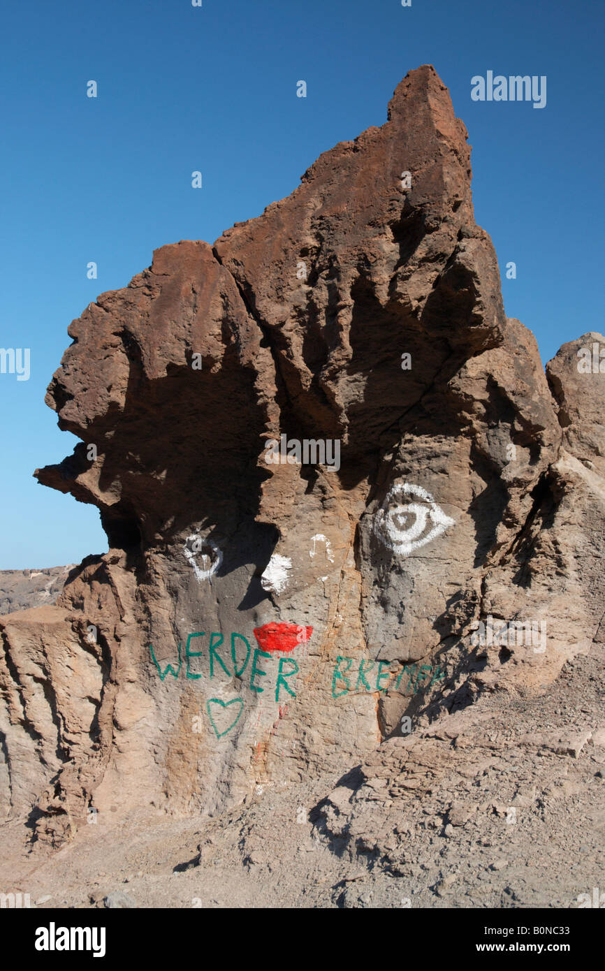 Rock shaped like face painted with eyes nose and lips. - Stock Image