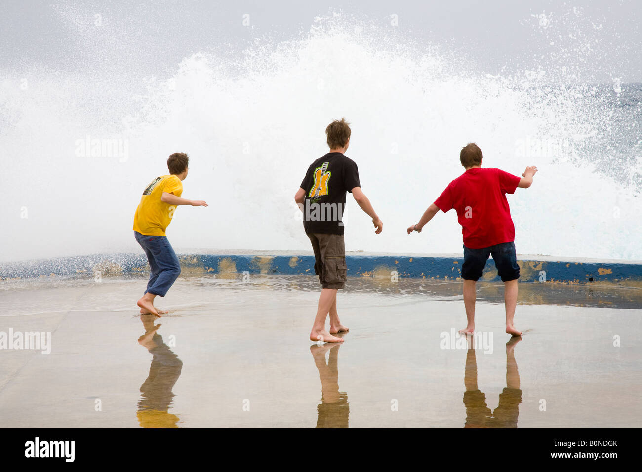 Breaking waves _Three Teenagers Dodging Waves on the seafront at Silema Malta - Stock Image