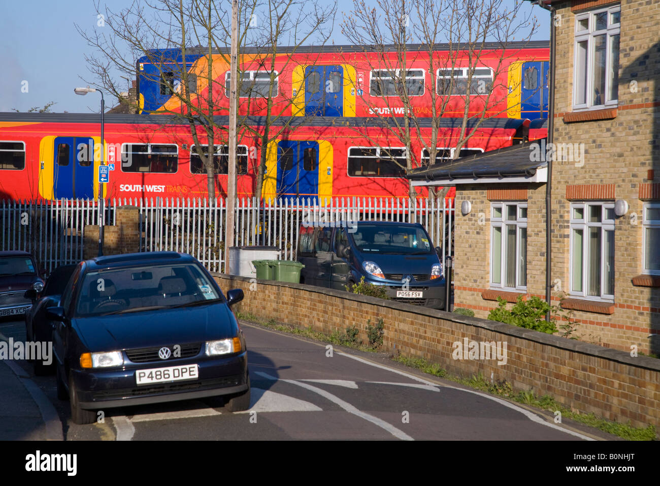 Two passing trains passing in a residential area, on different tracks, and near parked cars. Twickenham, West London. - Stock Image