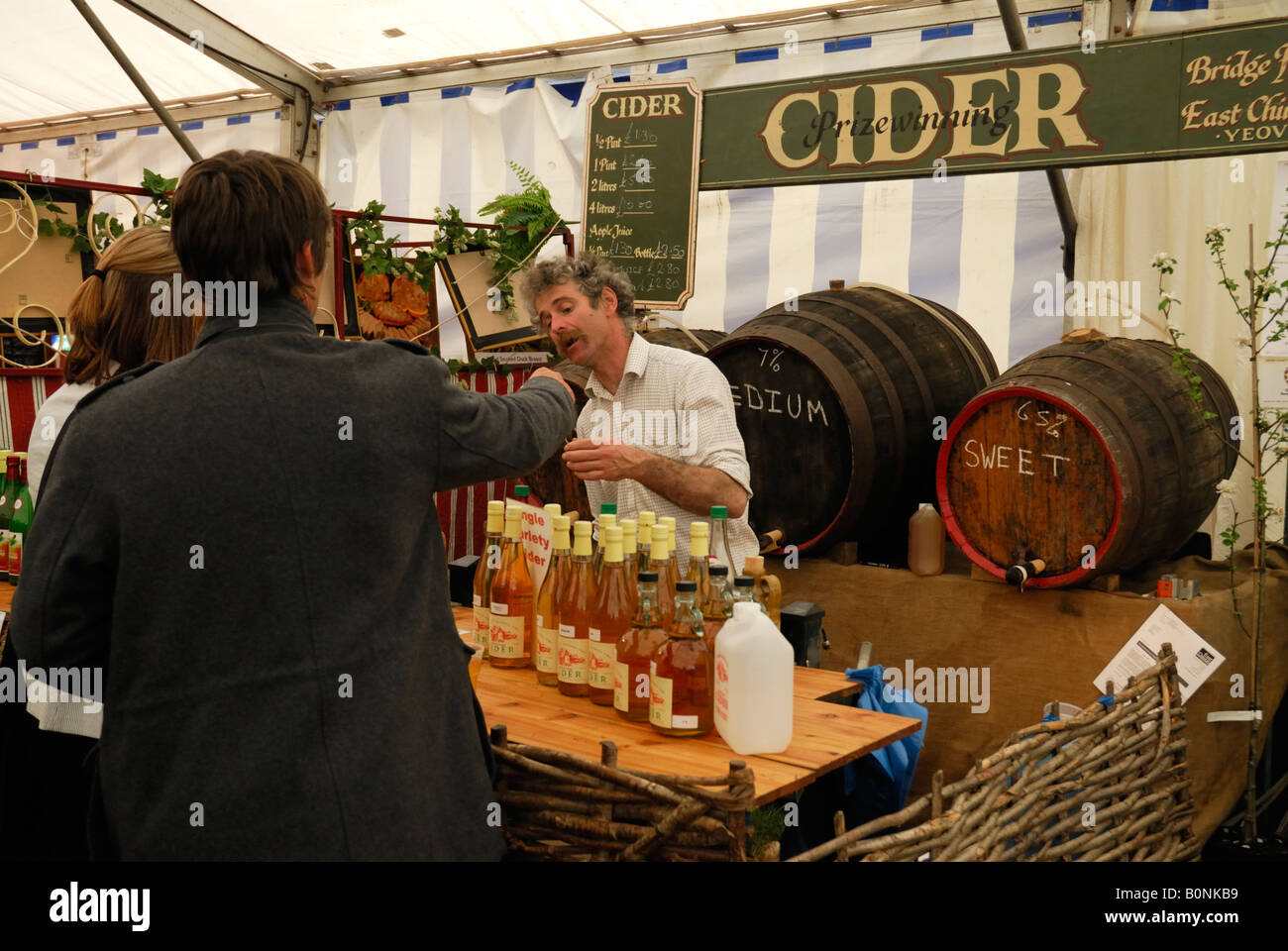 Couple buying cider from a stall at the Devon County Show, Exeter, UK - Stock Image