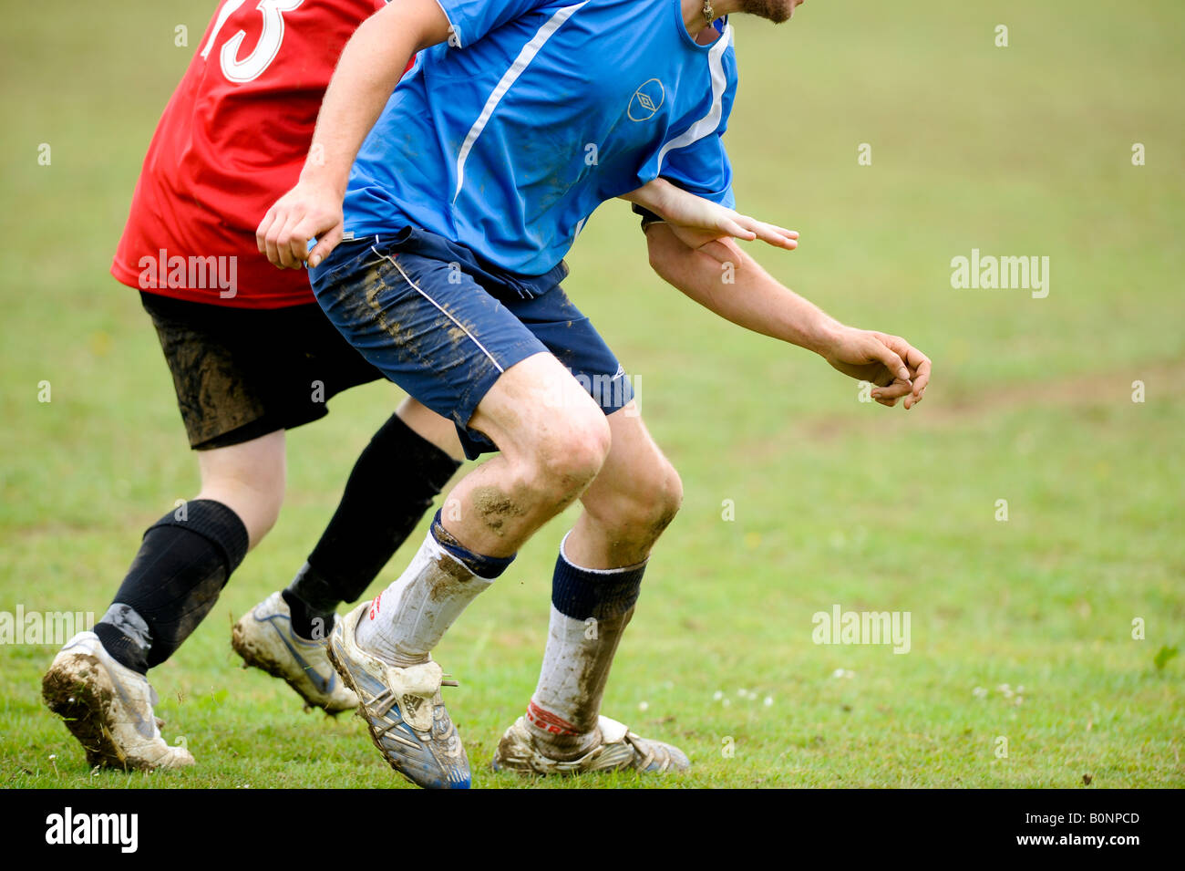 Park life football: two players battle for possession of the ball in a non league pub team clash. - Stock Image