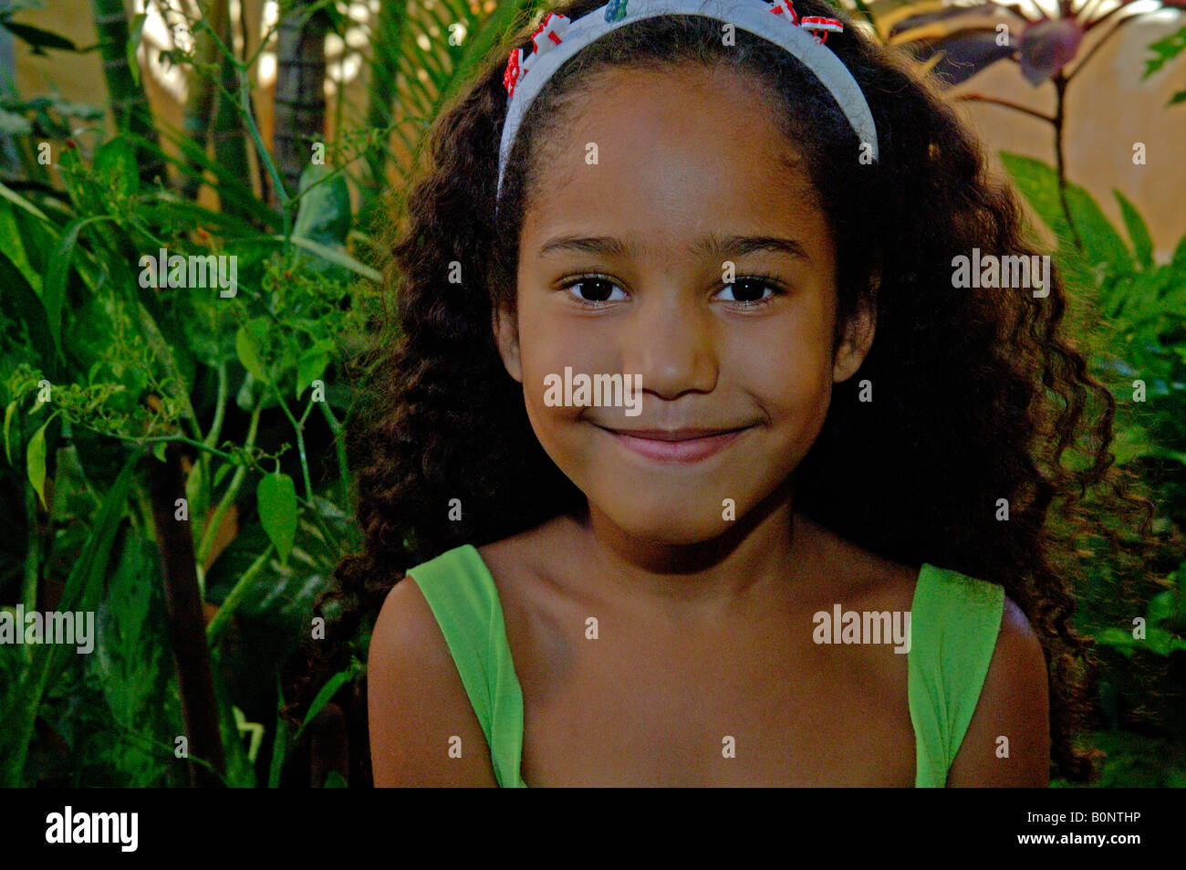 5eaf1a79b406c a young light brown, brunette Brazilian girl with long curly hair, smiling  and wearing a light green t-shirt