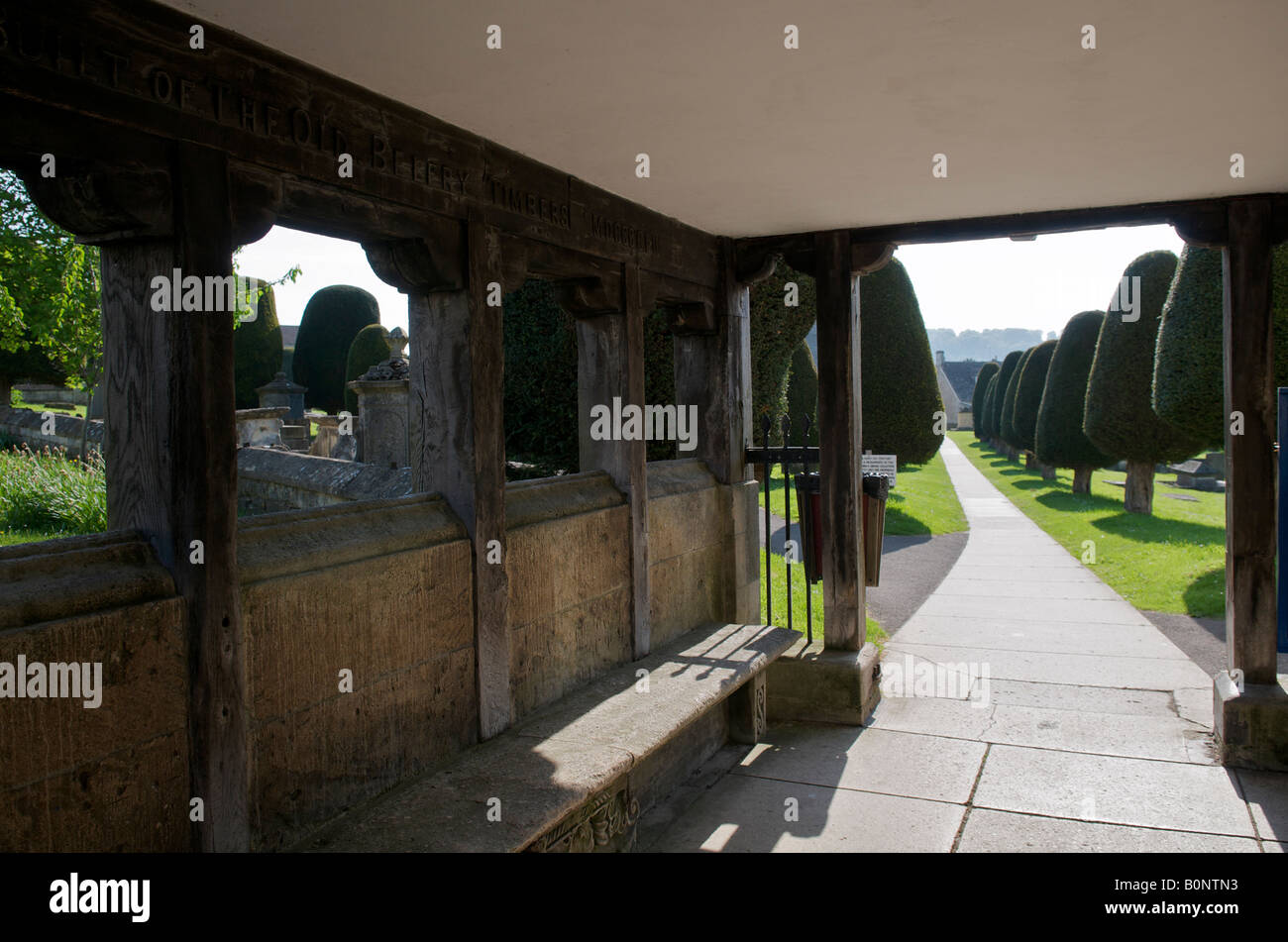 Yew trees in St Mary's church at Painswick in the Cotswolds looking through the lych-gate - Stock Image