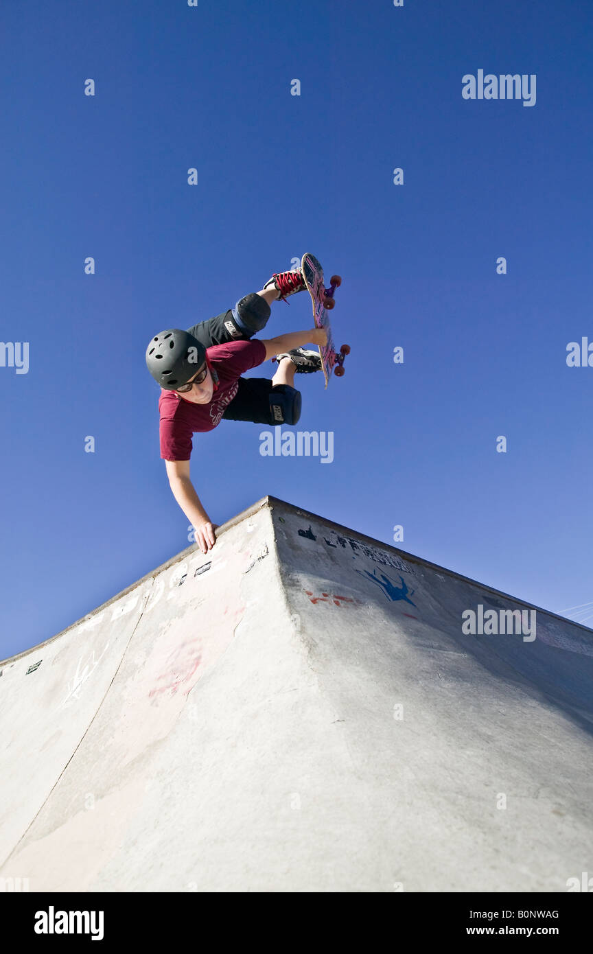 Teenage girl performs a balancing trick in a skateboard park - Stock Image