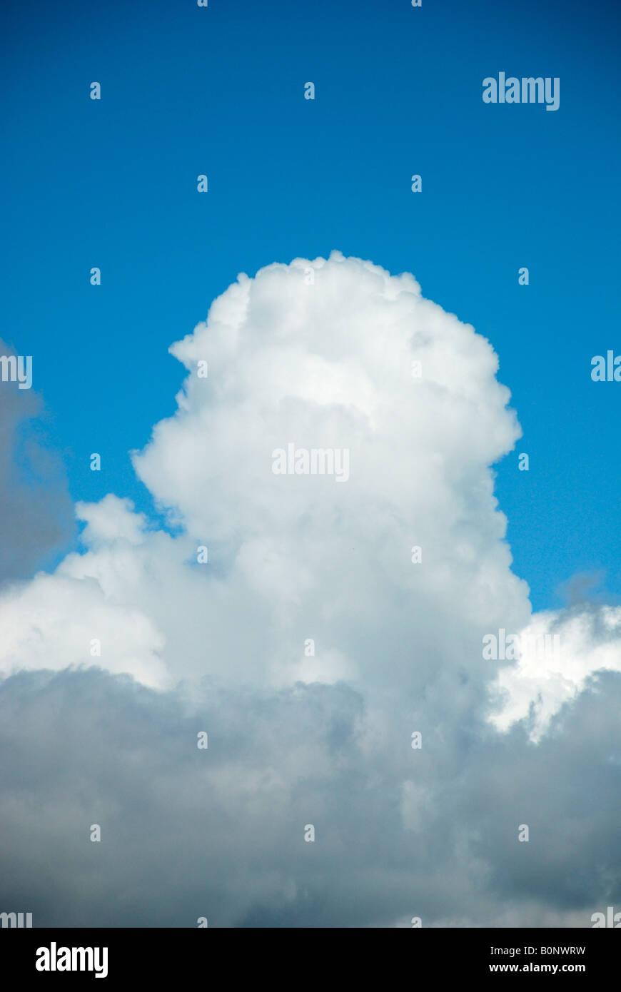 large cloud building against blue sky - Stock Image