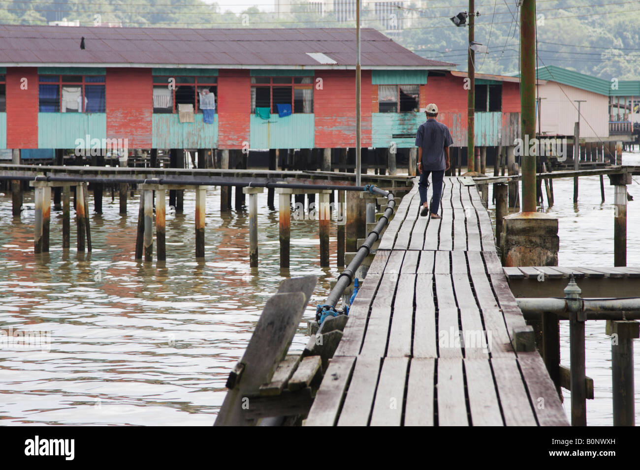 Man Walking Along Walkways Of Stilt Village Of Kampung Ayer, Brunei - Stock Image