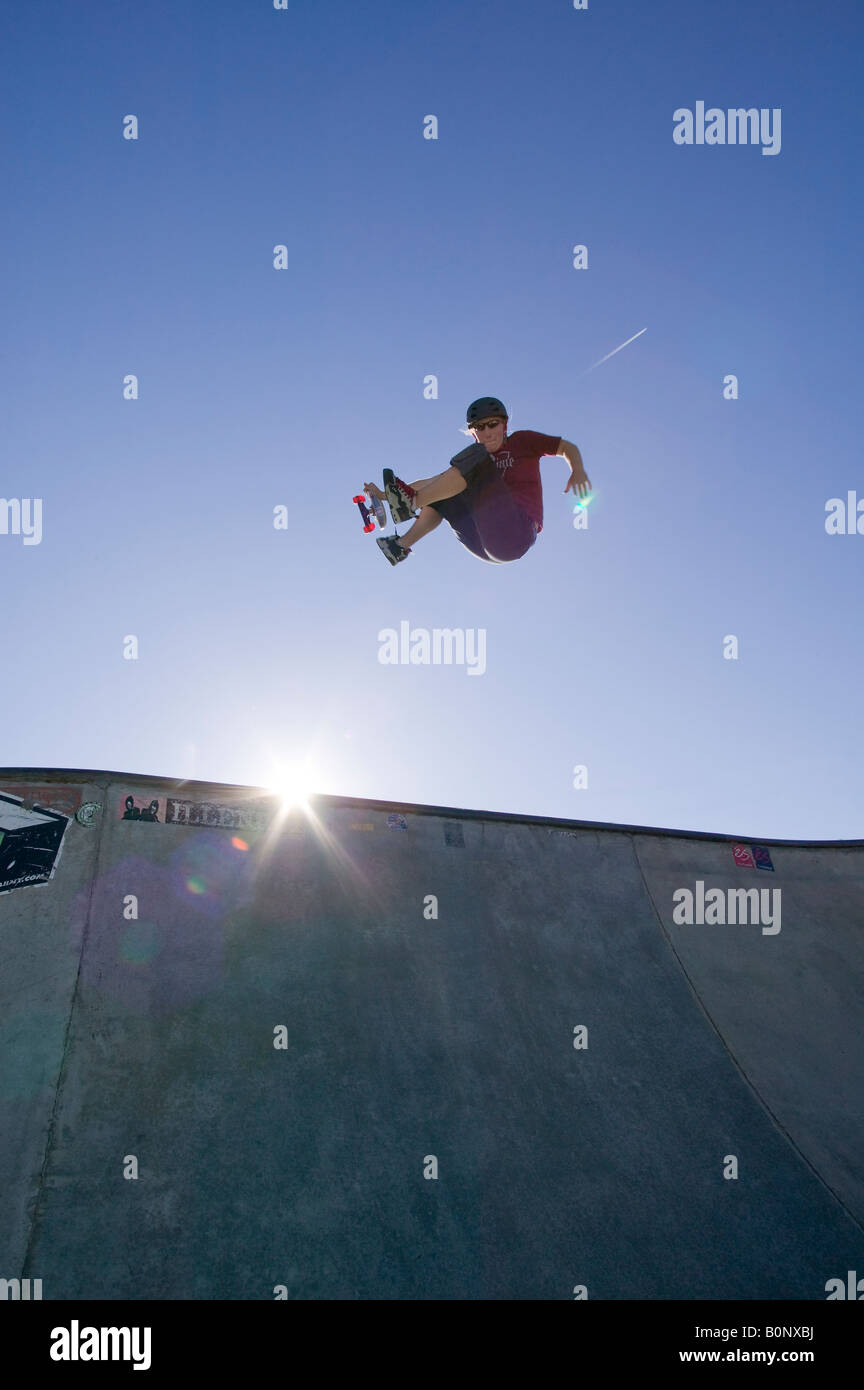 Teenage girl performs a jump in a skateboard park - Stock Image
