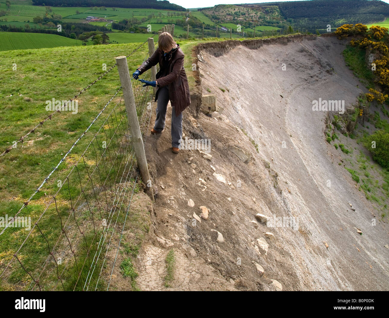 Woman negotiating a difficult country footpath undermined by a landslip - Stock Image