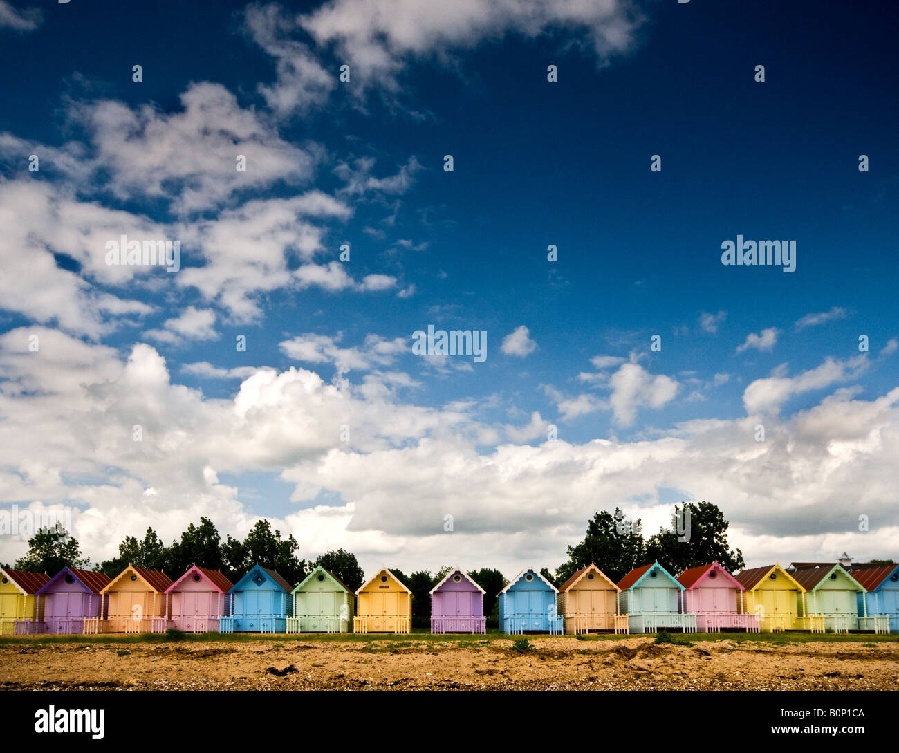 A row of colourful Beach Huts on West Mersea beach in Essex. - Stock Image