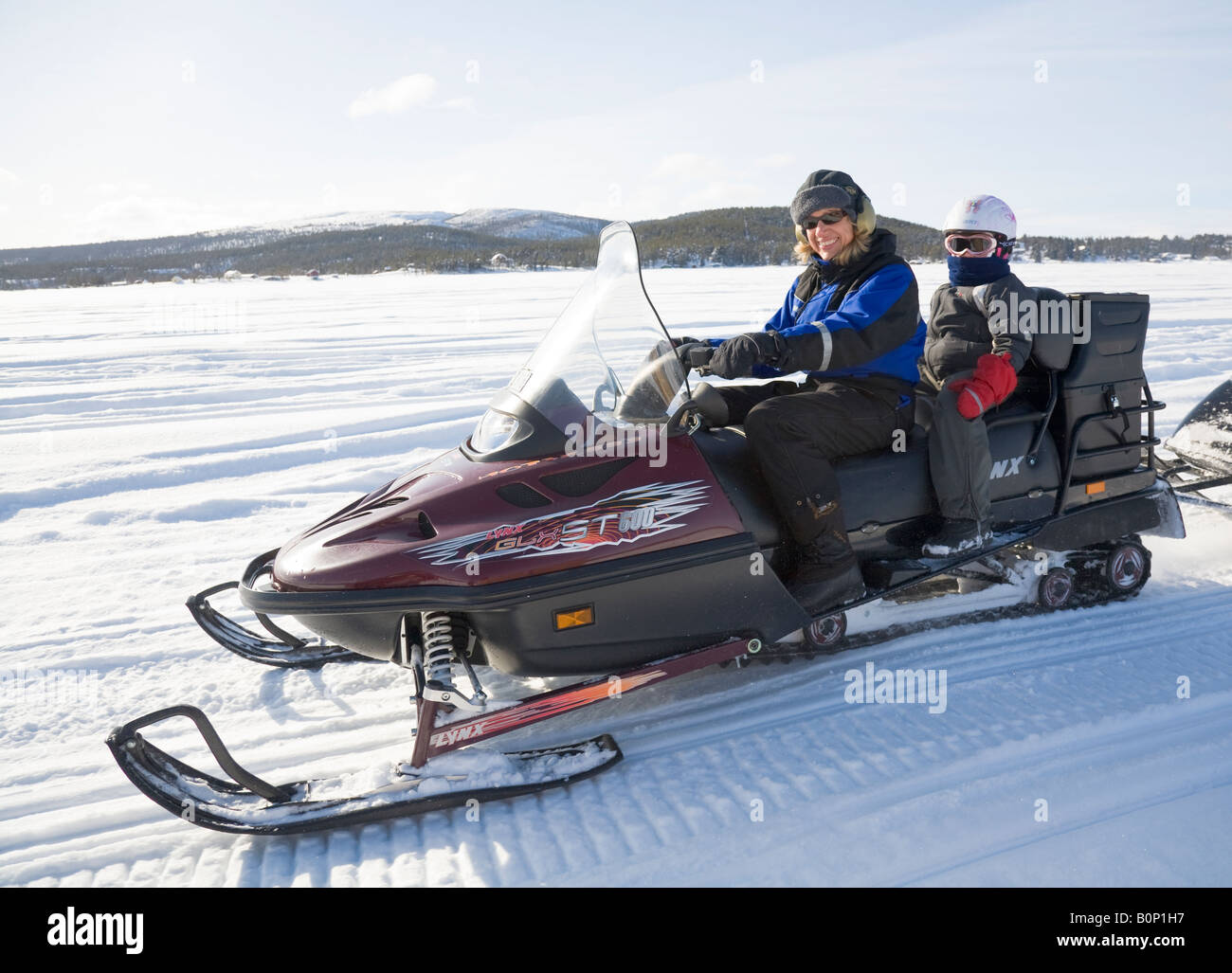 A woman in her fourties rides a Lynx snowmobile in snowy Lapland, a six years old girl is sitting on the back seat - Stock Image