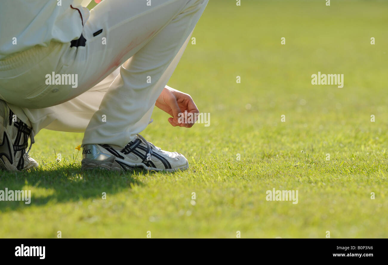 A fielder crouches waiting for action at cricket match in East Sussex. Picture by Jim Holden. - Stock Image
