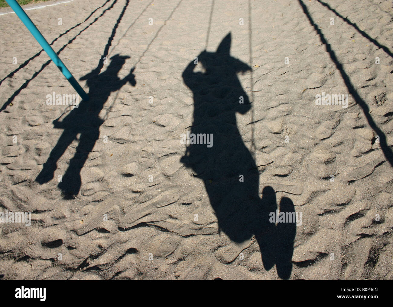 shadow of parent and child on swing wearing Halloween costumes - Stock Image
