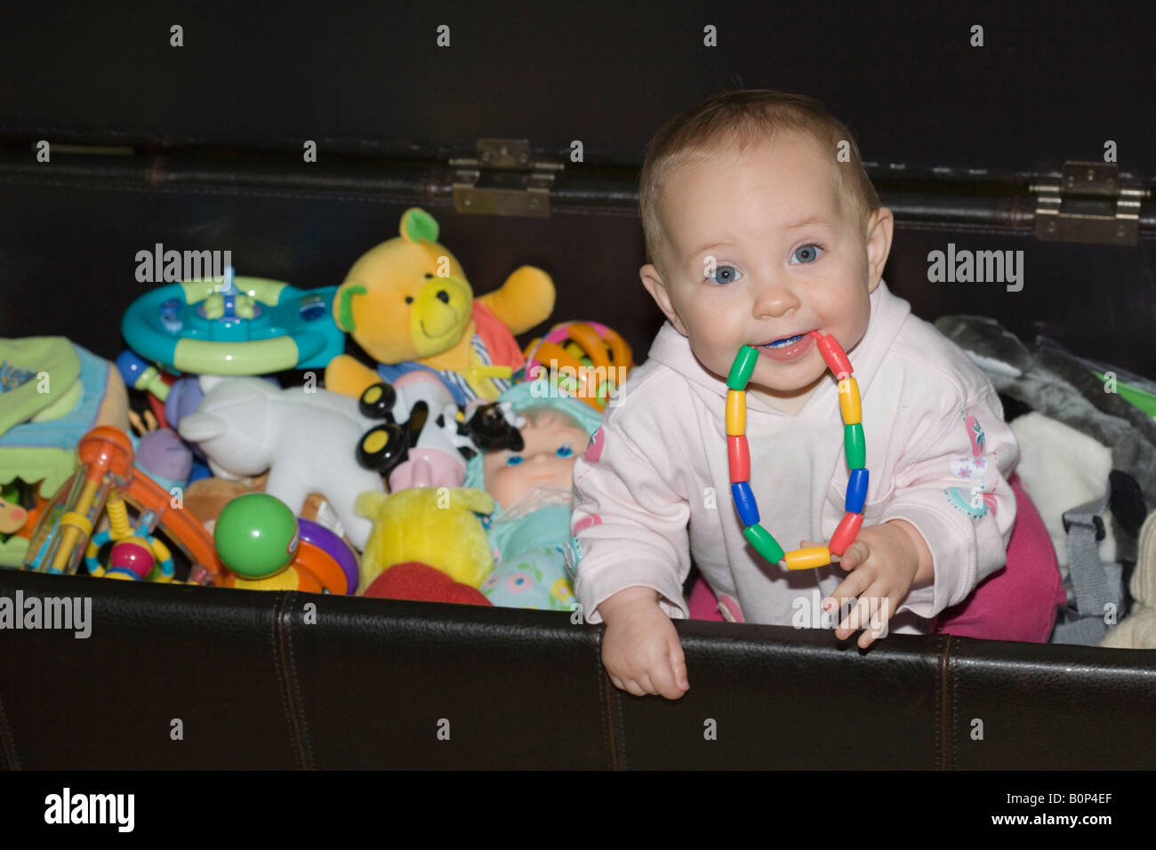 9 Month Old Baby Girl With Colourful Ring Teether In Her Mouth