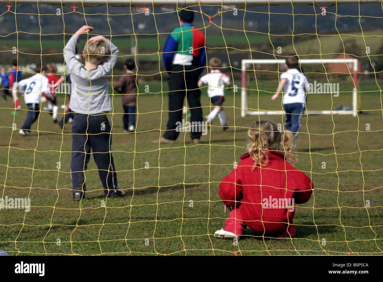 little girl playing in goal during a football match between children - Stock Image