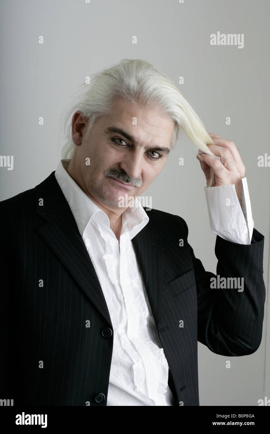 Man holding his long white hair - Stock Image