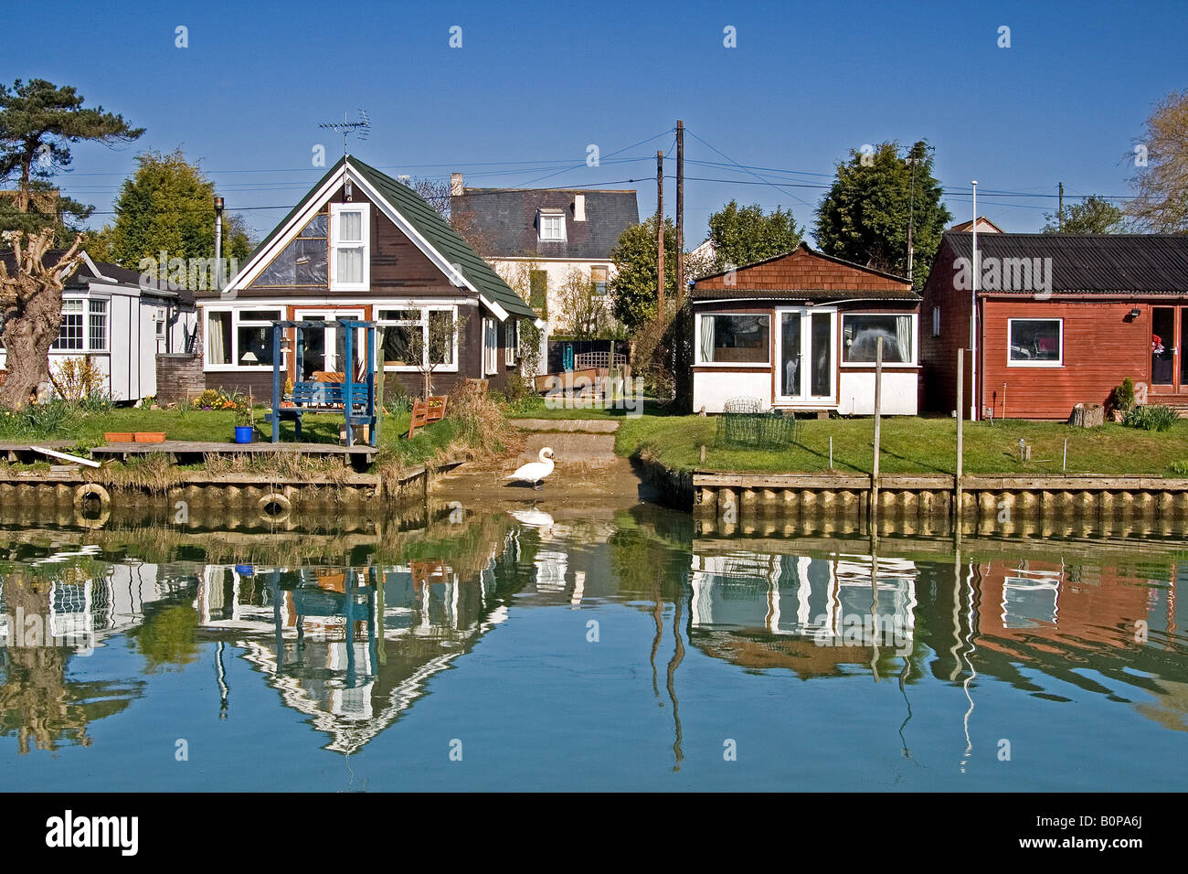 Houses reflecting on the Surfleet Resevoir in the Lincolnshire Fens Stock Photo