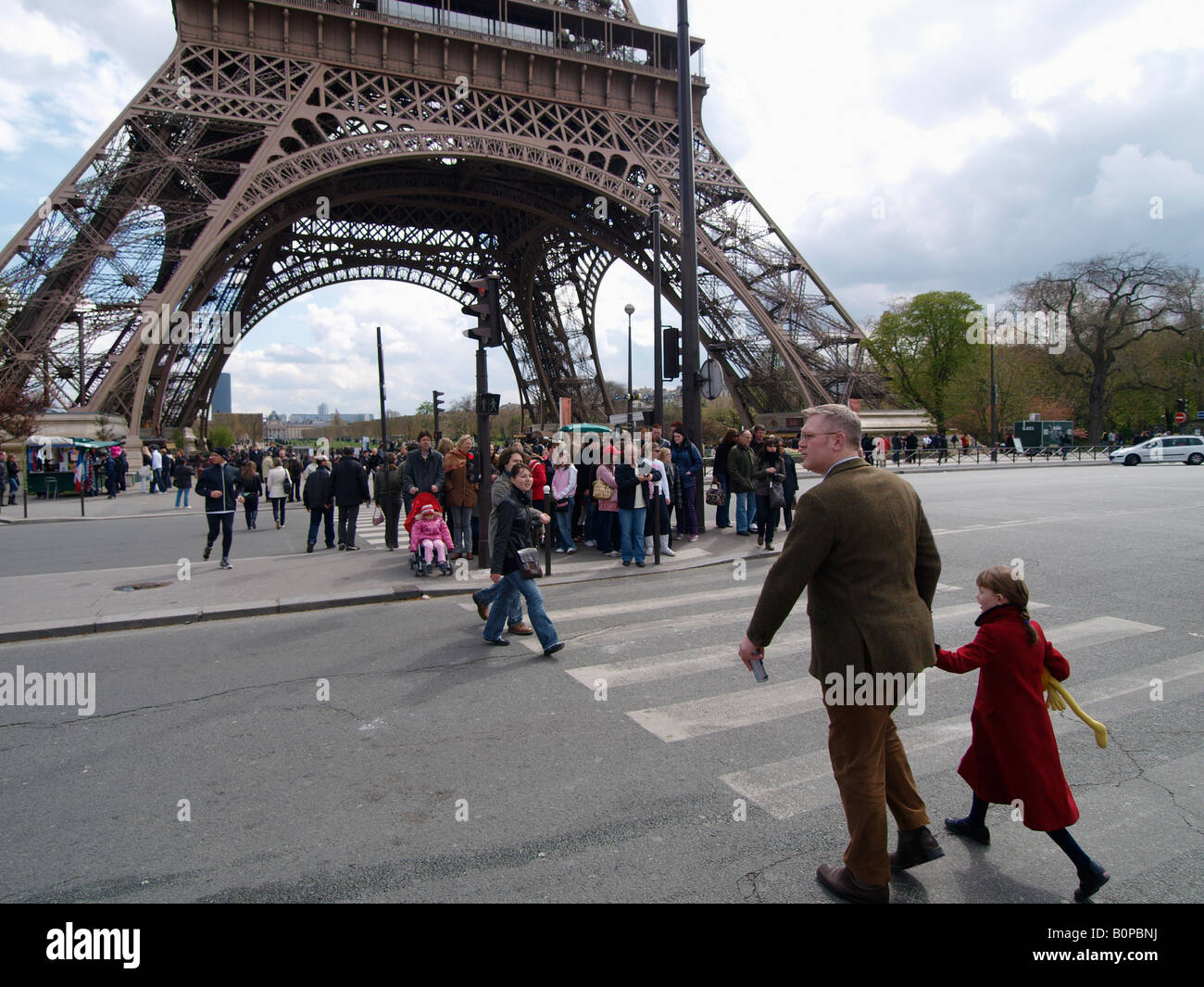 People tourists crossing the street near Eiffel Tower Paris France - Stock Image