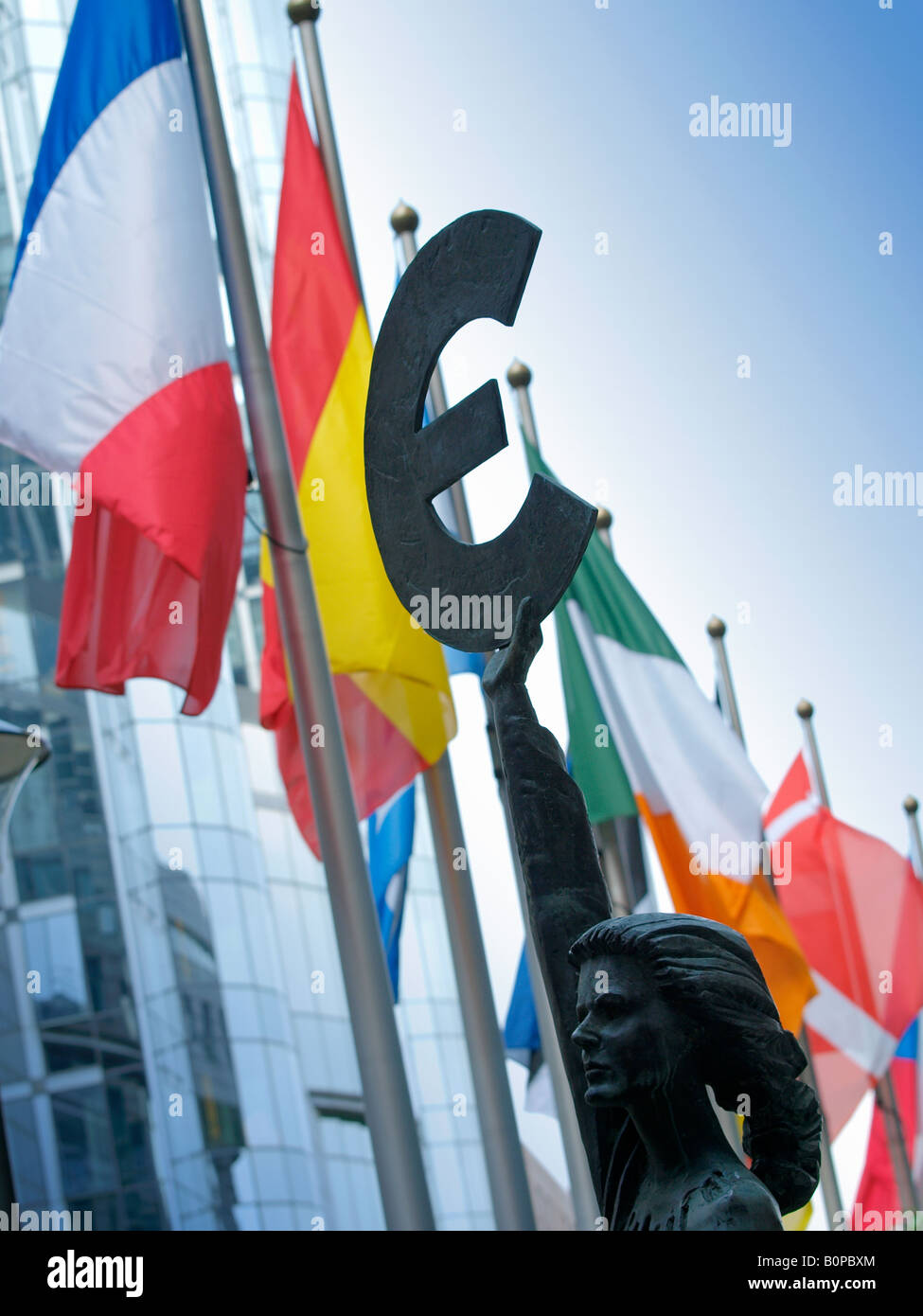 Bronze statue woman europa holding Euro currency sign Brussels Belgium with many national flags in the background - Stock Image