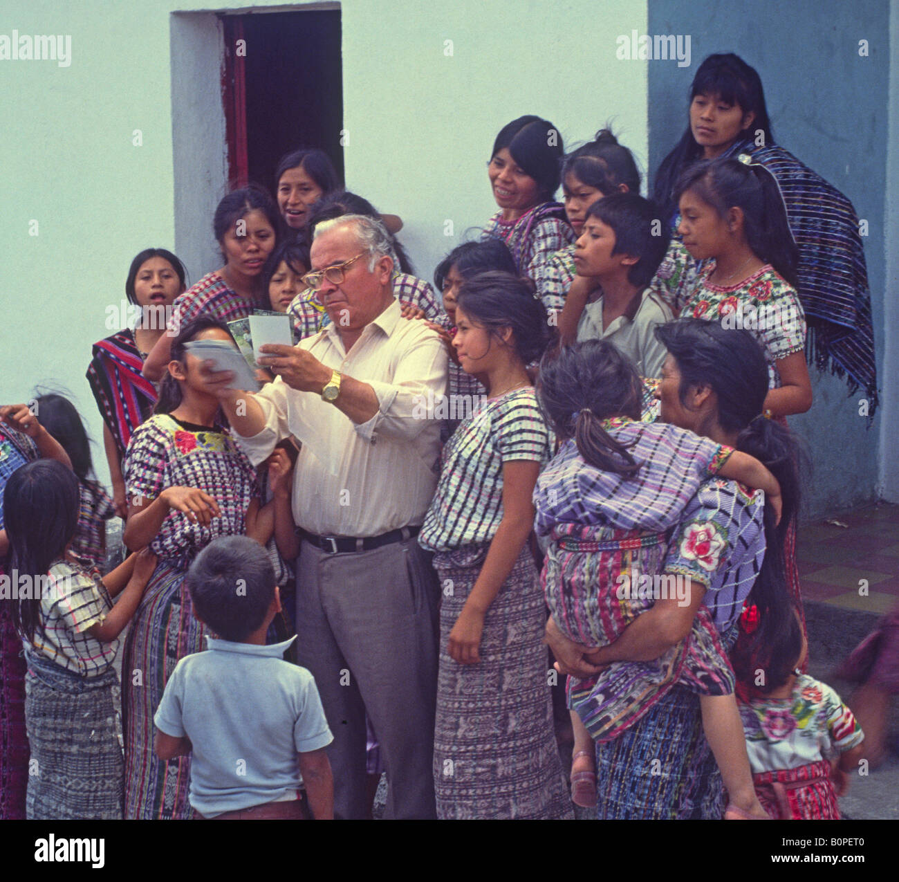 Man shows photo prints to Mayan Quiche women and children, Santiago Atitlan village, Guatemala - Stock Image