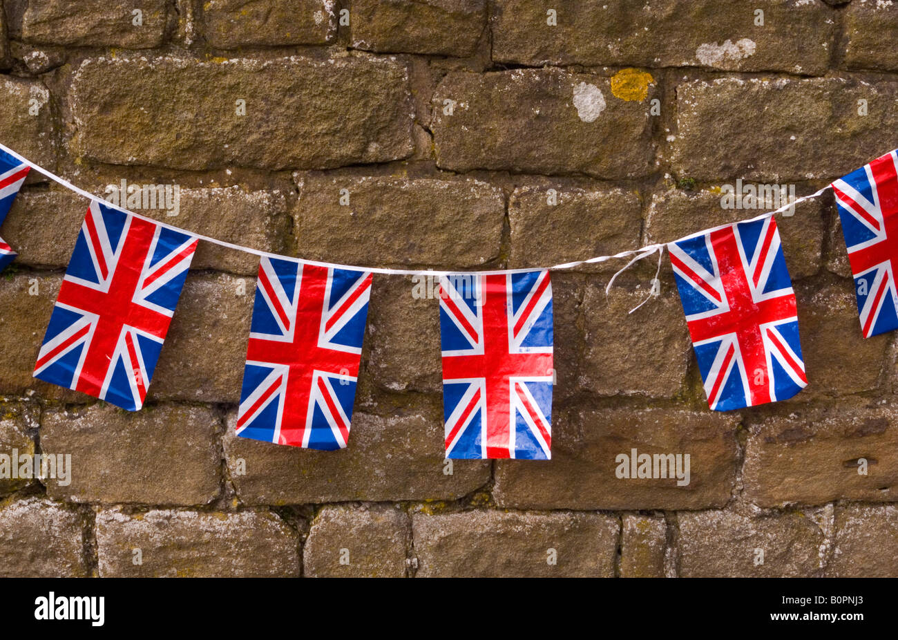 Close up view of Union Jack bunting flags with a stone wall behind - Stock Image