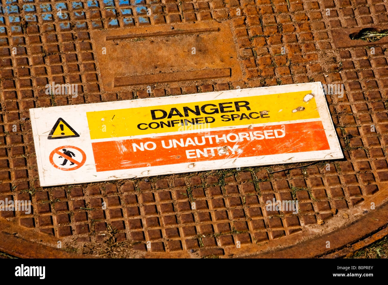 Restricted access manhole cover with warning sign - Stock Image
