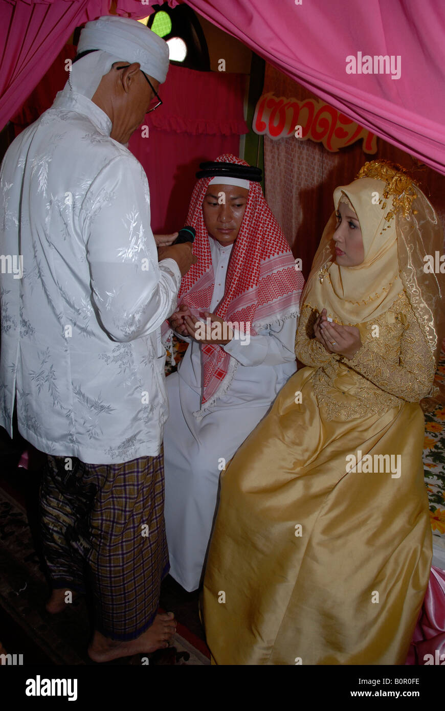 imam is blessing muslim bride and groom in their wedding day - Stock Image