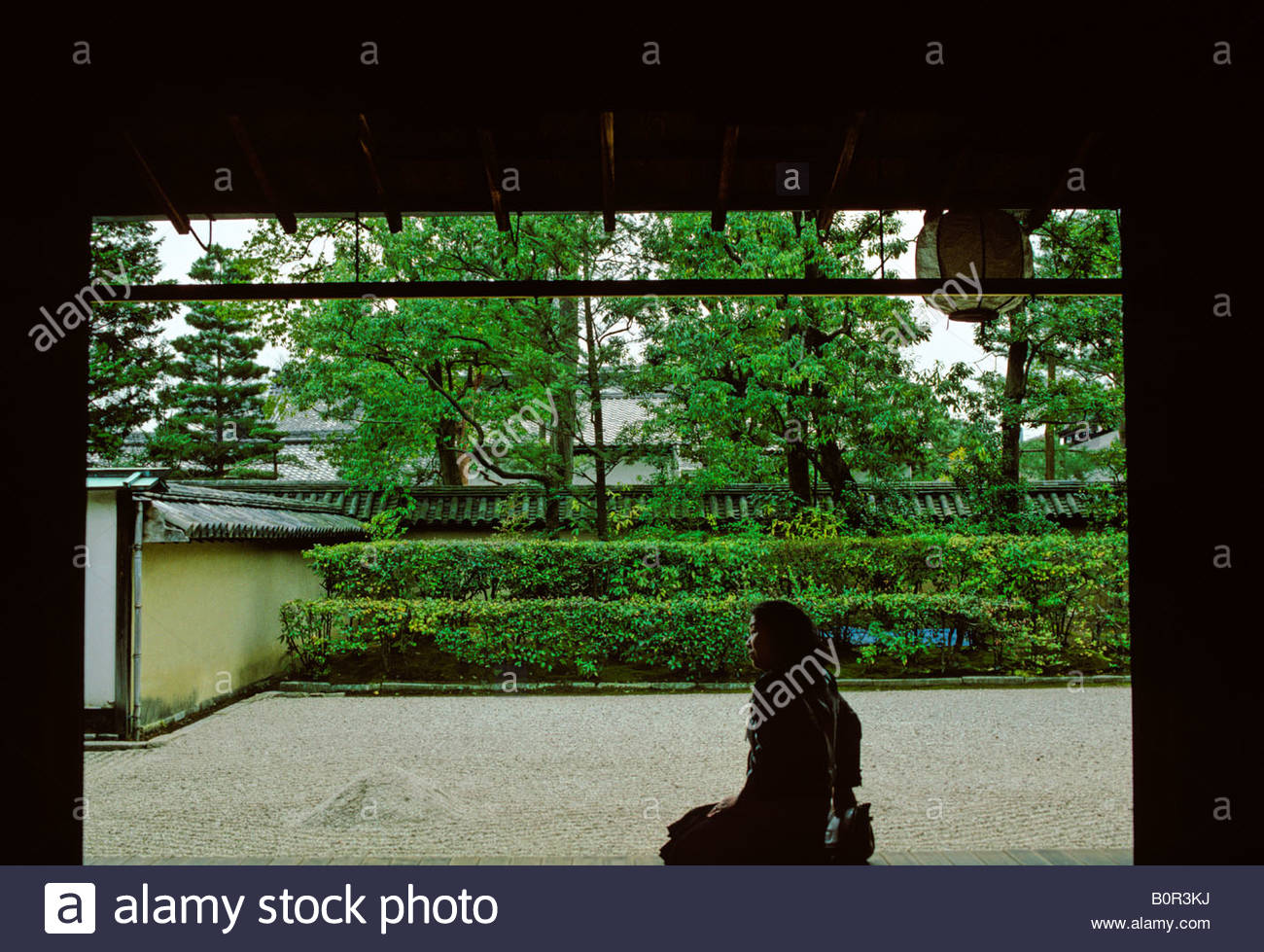 A young woman sits in front of Daisenji stone garden in Daitokuji temple, Kyoto, Japan - Stock Image