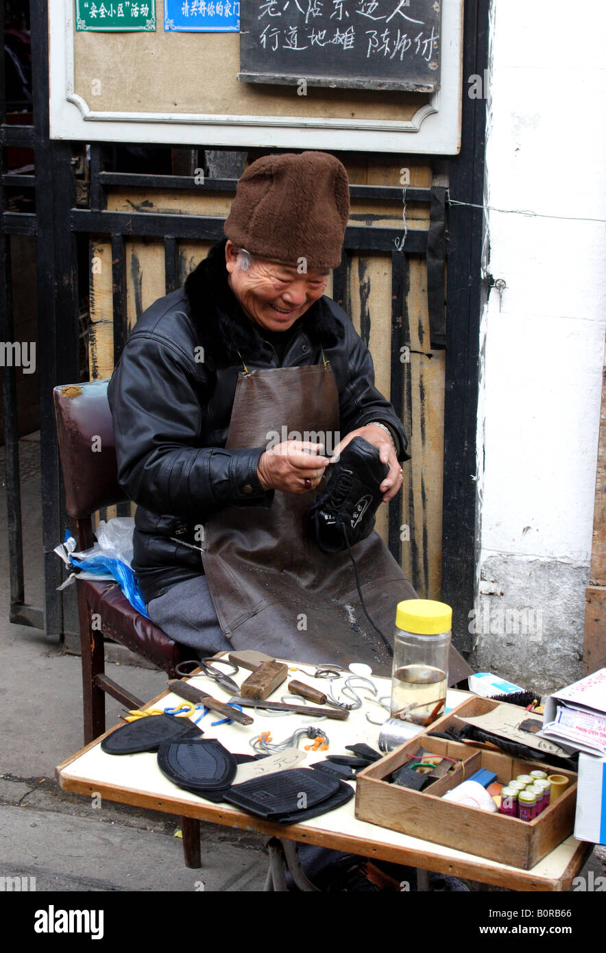 A cobbler works on the street in Shanghai - Stock Image
