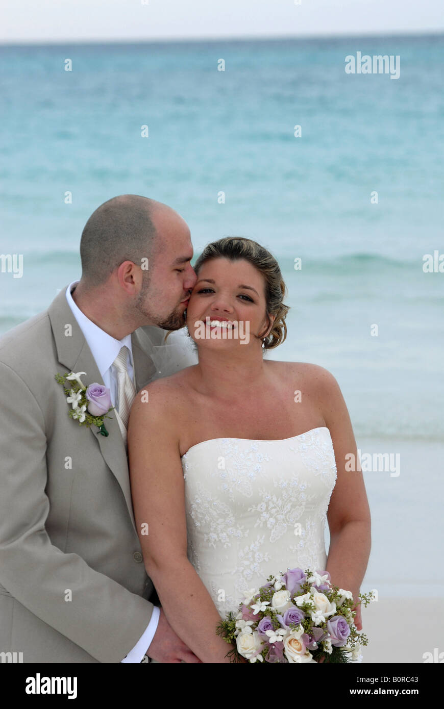 The bride in an ivory wedding dress and groom in a sand colored ...