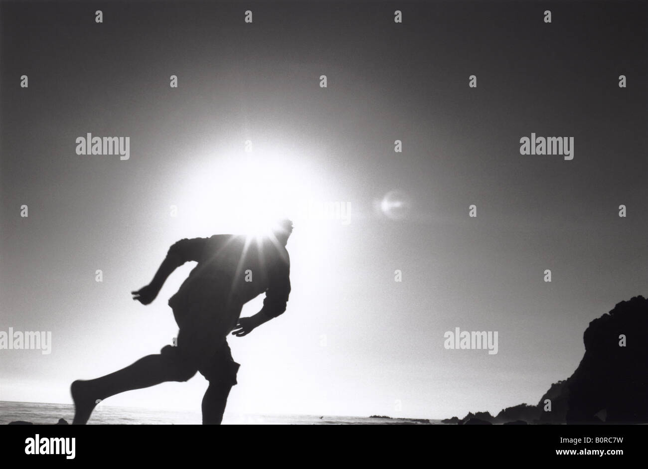 silhouette of man running on beach with sun behind his head flare glare blocking glow black and white - Stock Image