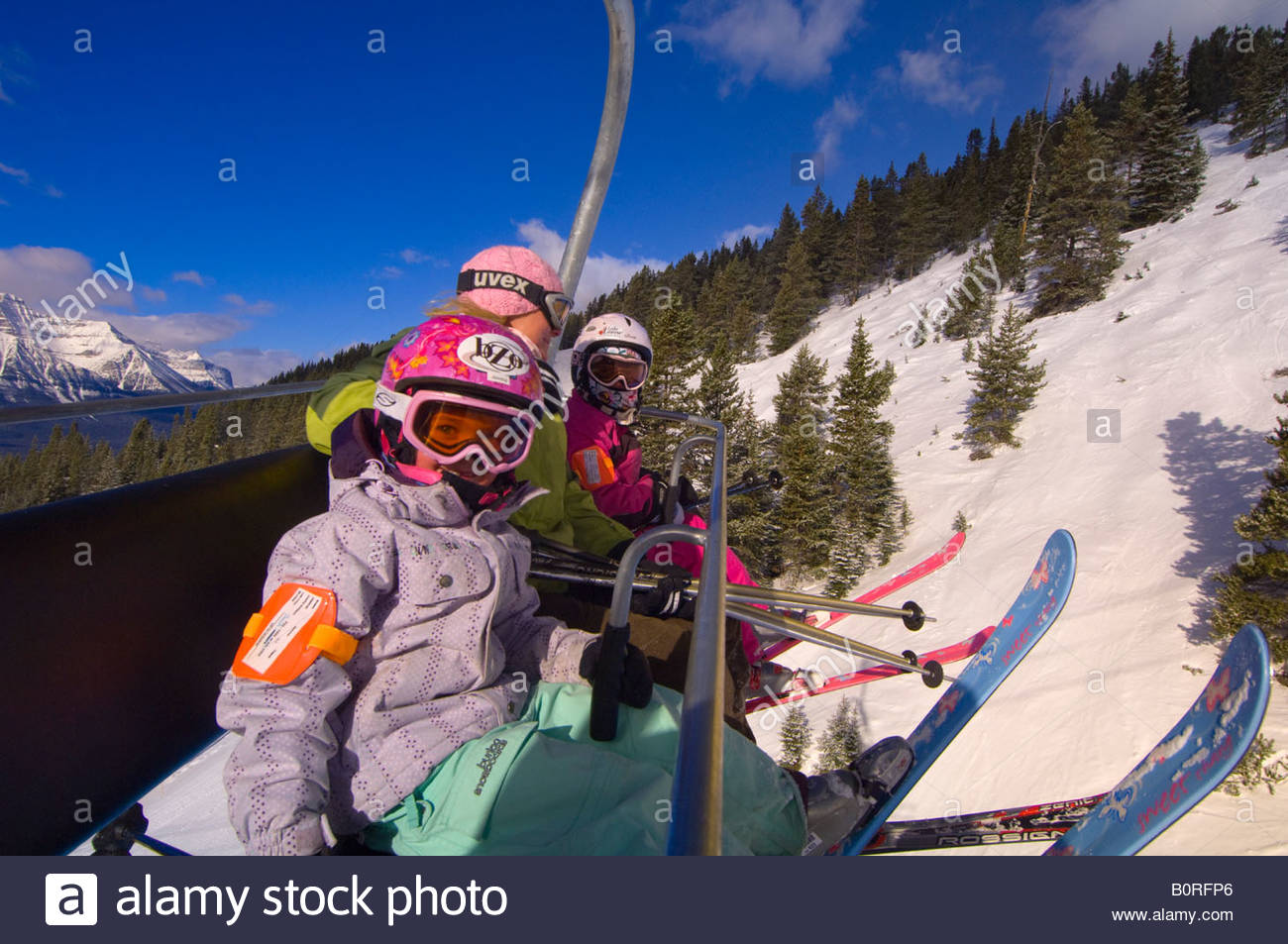 Children and their mother ride the chairlift at Lake Louise Mountain Resort Lake Louise Banff National Park Alberta - Stock Image