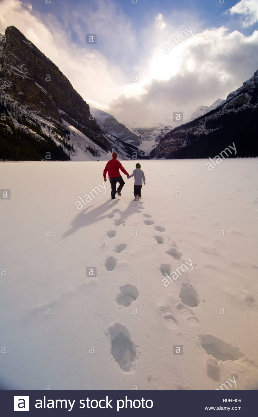 A father and son walking on Lake Louise with the Chateau Lake Louise Hotel in the background Banff National Park - Stock Image