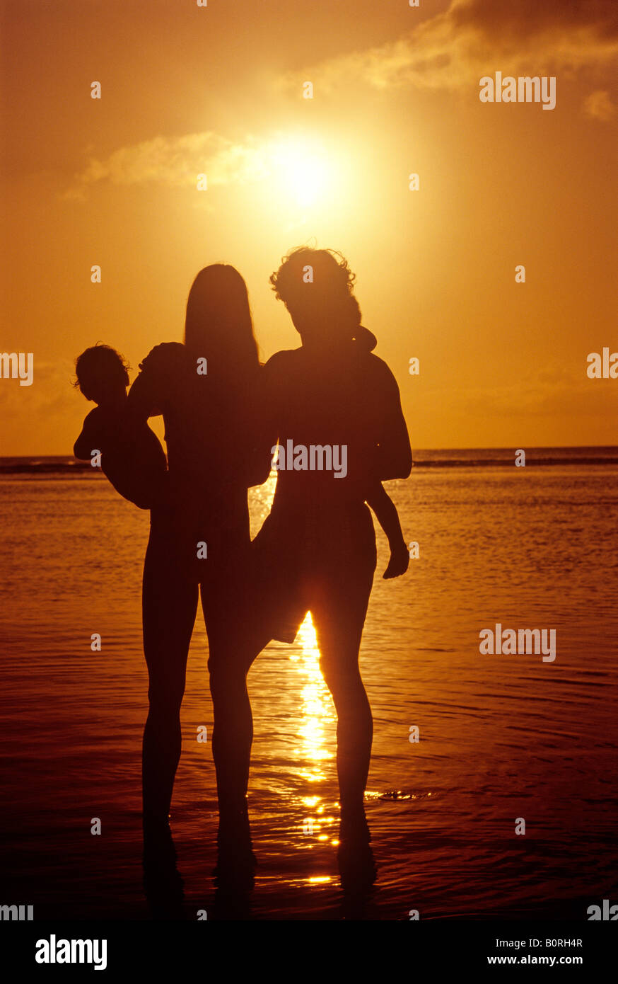 portrait of young family enjoying leisure time at sunset - Stock Image