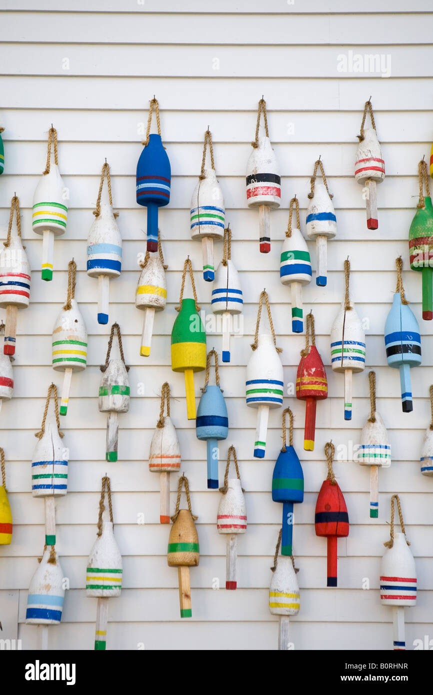 many colorful lobster buoys hang on wall in Maine - Stock Image