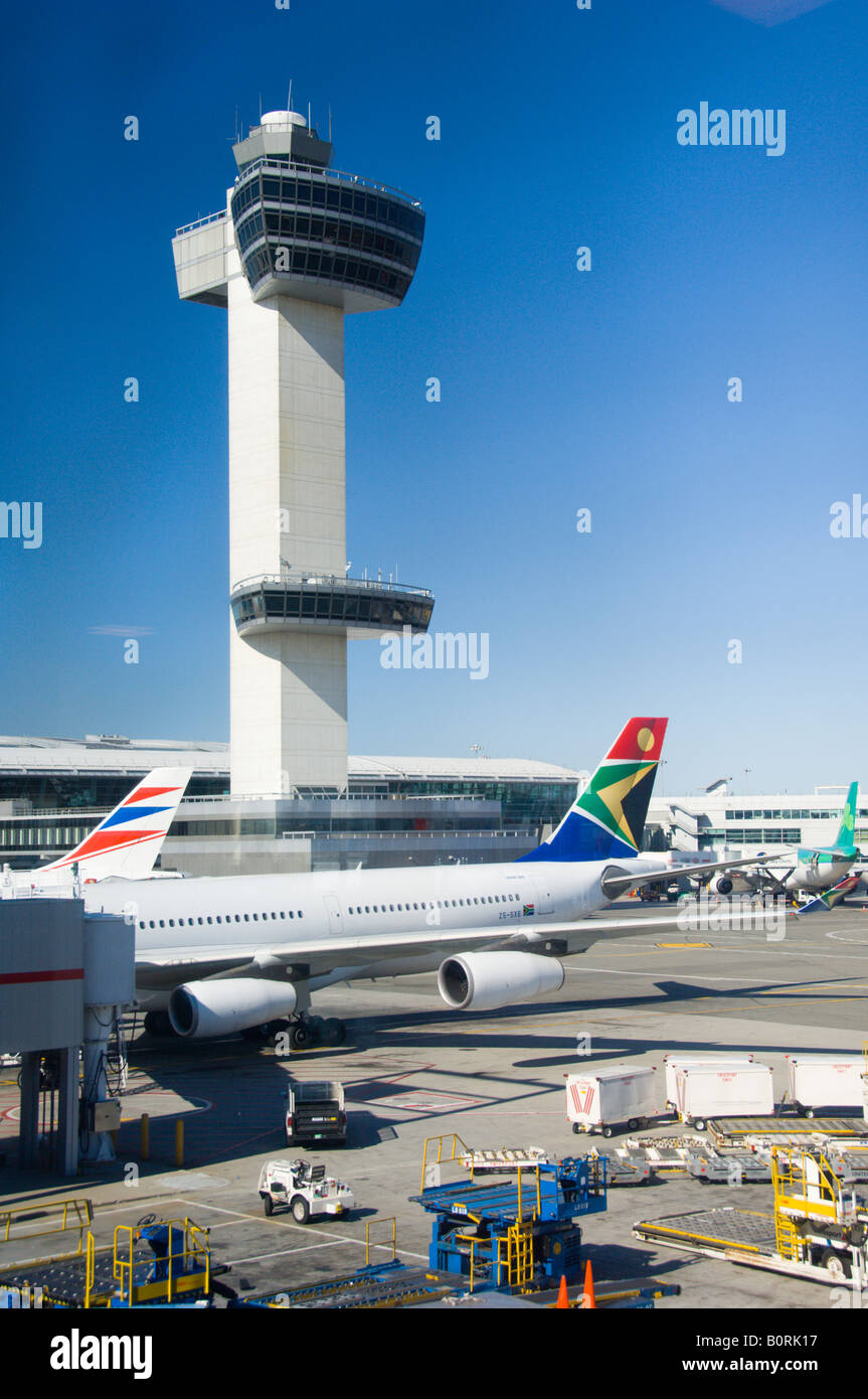 The JFK International airport air traffic control tower with airplanes parked at the terminal - Stock Image