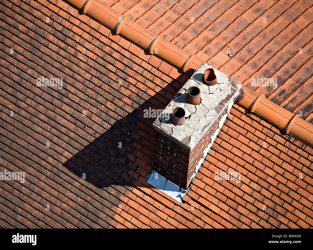 Chimney pots with cracked concrete rendering on tiled roof Belgium - Stock Image