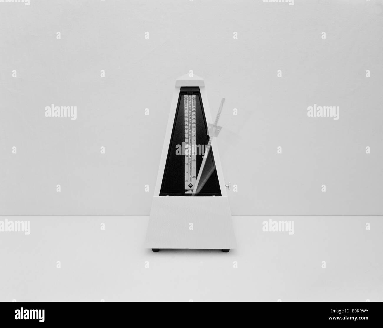 1 of a series of landscape monochrome images this one is of a moving metronome shot against a plain background - Stock Image