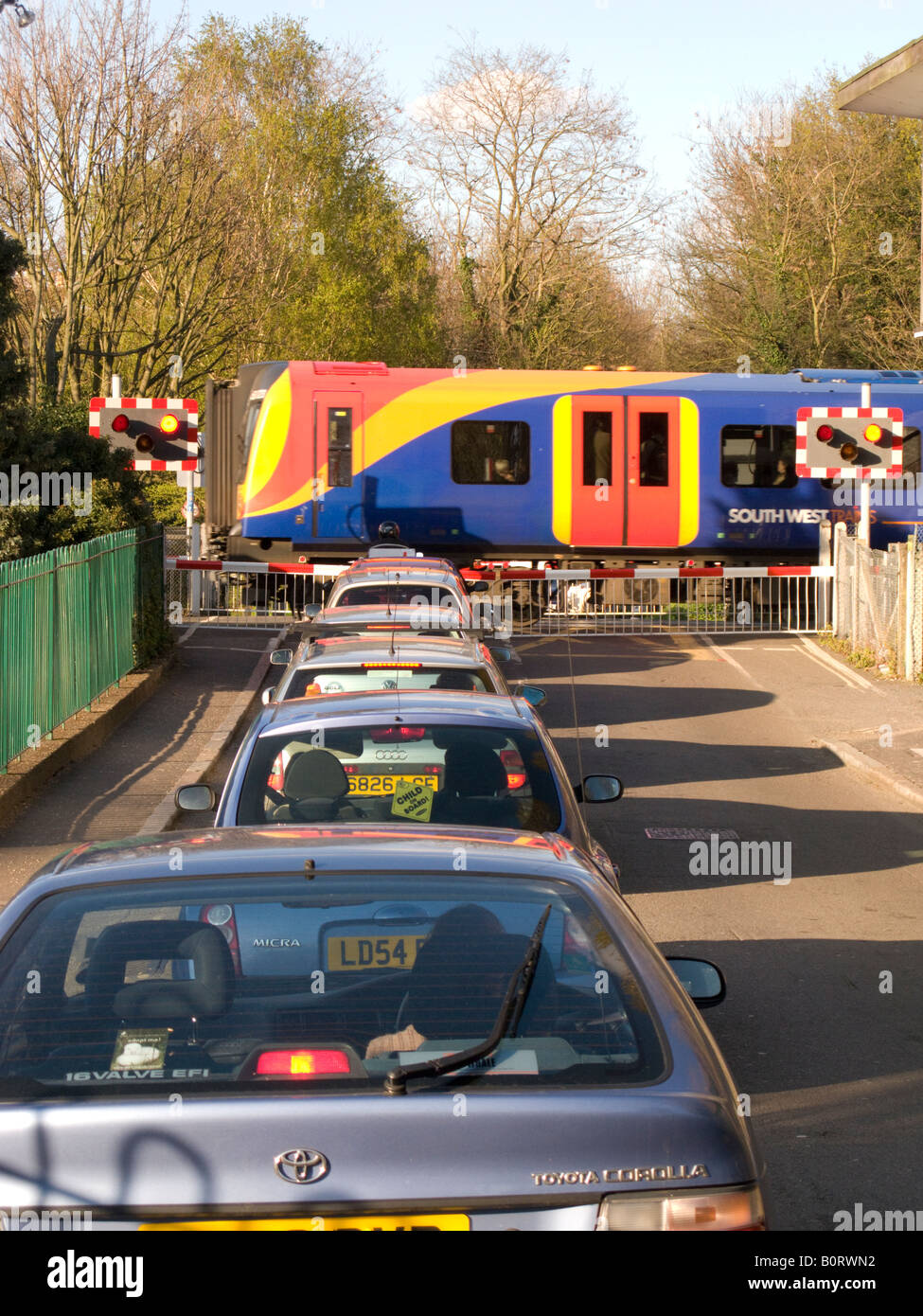 Cars wait at a railway level crossing barrier as train passes through the crossing. - Stock Image