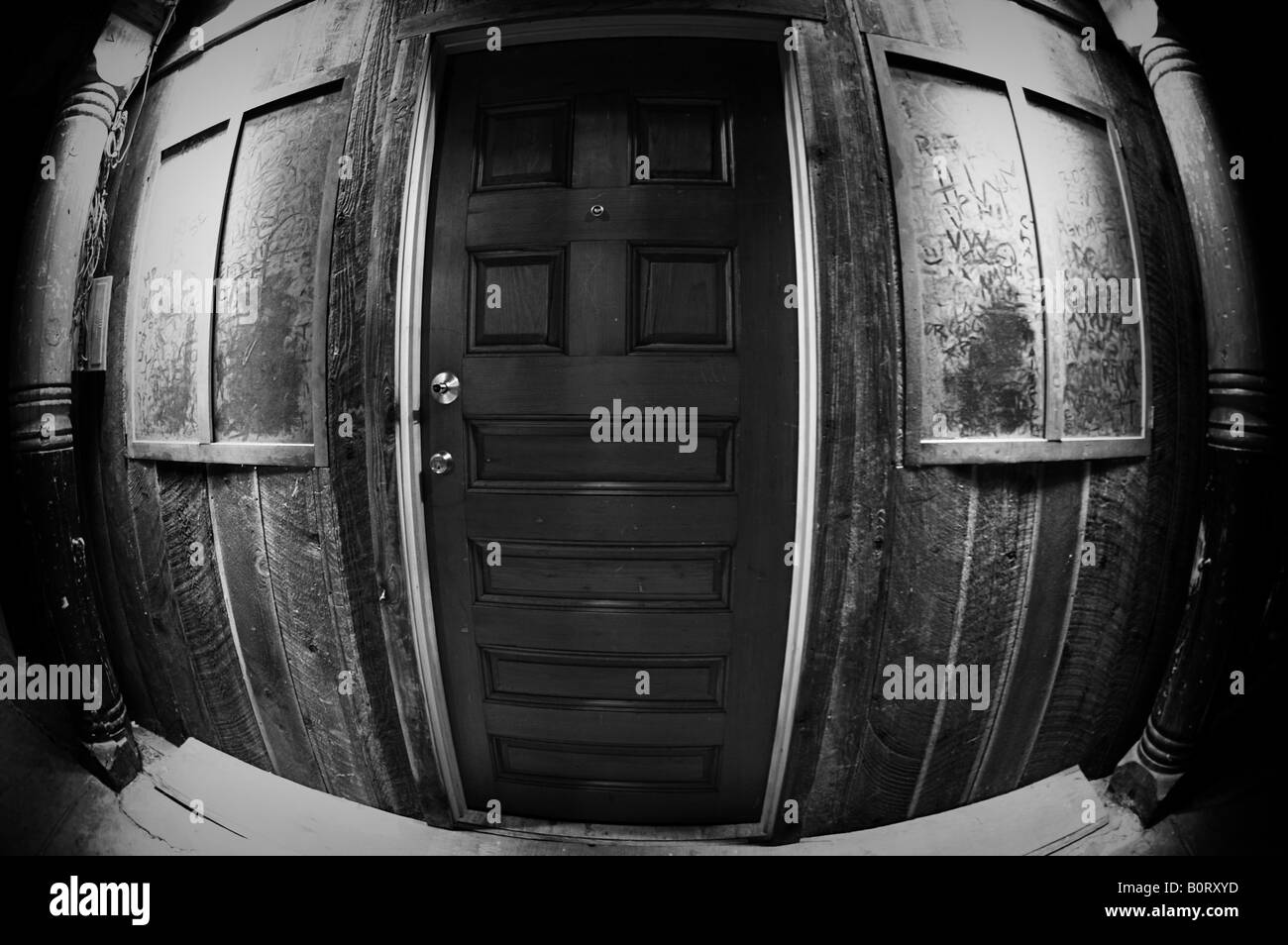 Creepy black-and-white door covered in dust with fish-eye lens. - Stock Image