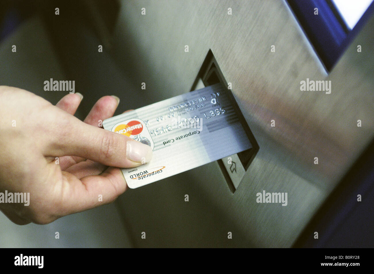 Paying with credit card by a automated teller machine - Stock Image
