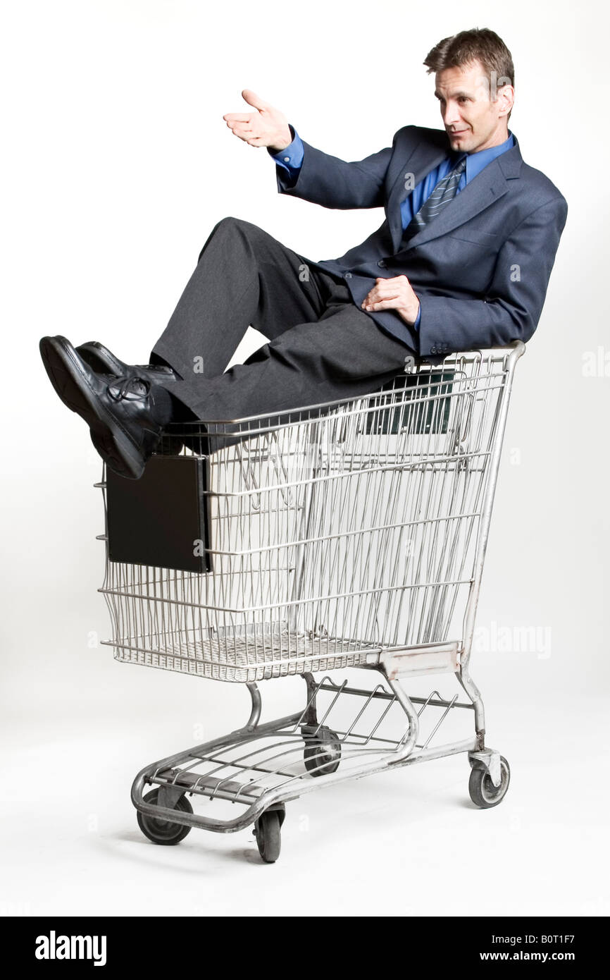Businessman sitting on a shopping cart - Stock Image